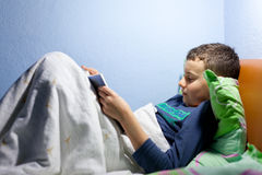 Kid reading a book at bedtime. Portrait of a boy reading a book at bedtime, lying in his bed Stock Images