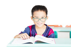 Kid reading book in classroom. Smart kid reading book in classroom Stock Photo