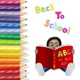 Kid reading a book on a colored pencils background. Kid reading a book on a multicolored pencils background Royalty Free Stock Image