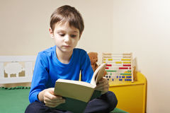 Kid reading a book at home. Little kid reading a book at home Stock Photos