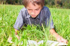 Kid reading a book outdoor Stock Image