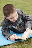Kid reading book outdoors. Kid in casual reading book outdoors Stock Photography