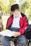 Kid reading book in park. Kid in red jacket reading book in autumn park Royalty Free Stock Photo