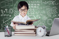 Kid reading books with clock on the table Royalty Free Stock Photo