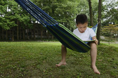 Kid reading. Chinese kid sitting on hammock , reading in park Stock Image