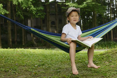 Kid reading. Chinese kid sitting on hammock , reading in park Royalty Free Stock Photos