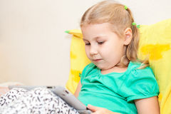 Kid reading electronic book. Little Caucasian child reading on e-reader pad Stock Photography
