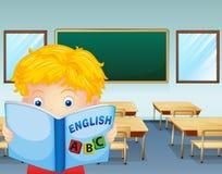 A kid reading inside the classroom Stock Photo