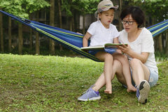 Kid reading with mom together. Chinese kid sitting on hammock , reading in park with mom together Royalty Free Stock Images