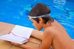 Kid reading near pool Stock Photo
