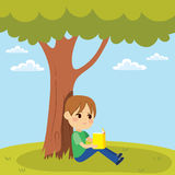 Kid Reading Under Tree Stock Image