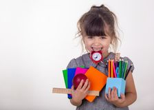 Kid ready for school. Cute clever child in eyeglasses holding school supplies: pens, notebooks, scissors, alarm clock and apple. royalty free stock photos