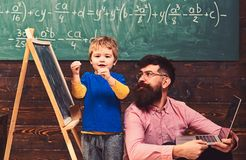Kid reciting a poem while teacher listens attentively. Cool guy in pink shirt sitting on floor next to standing kid. Kid reciting a poem while teacher listens stock photo