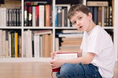 Kid with red book in the library. Looking at camera. Royalty Free Stock Images