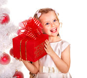 Kid with red Christmas gift box. Child with gift box near white Christmas tree. Isolated Royalty Free Stock Photos