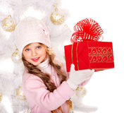 Kid with red Christmas gift box. Child in hat and mittens holding red  gift box near white Christmas tree. Isolated Stock Photo