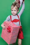 Kid in red costume of dwarf holding Christmas gift and throws Santa Claus cap. Naughty child Royalty Free Stock Images