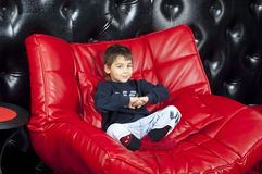 Kid on a red leather sofa Royalty Free Stock Photography