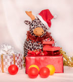 Kid in the red Santa Claus suit sitting with reindeer doll among Stock Photos