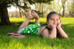 Kid Relaxing Outside. A young girl laying in the grass relaxing and enjoying the spring weather Stock Images