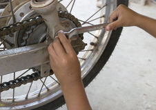Kid repair chain of motorcycle. Kid hands use wrench to repair chain of motorcycle stock photo