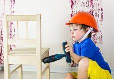 Kid repairing wooden chair Stock Photos