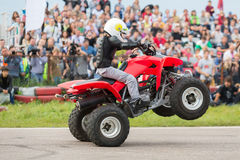 Kid rides on the rear wheels on a quad bike Stock Photo