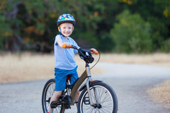 Kid riding bicycle. Cheerful little boy riding bicycle Stock Photo