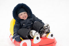 Kid is riding down the hills in the winter Stock Photos