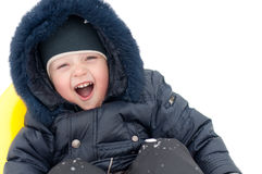 Kid is riding down the hills in the winter Stock Images