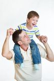 Kid riding father's shoulders. Kid son riding father's shoulders royalty free stock images