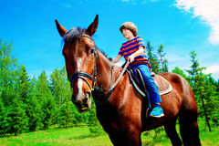 Kid is riding a horse Stock Photo