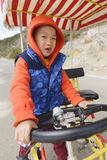 Kid riding quadricycle. Chinese kid trying to ride quadricyle alone Royalty Free Stock Image