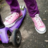 Kid riding a scooter. Feet Stock Images