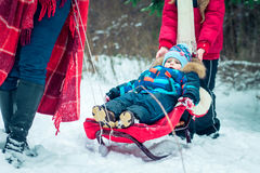 Kid is riding in a sleigh Stock Images