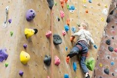 Kid rock climbing. Little active boy rock climbing at indoor gym royalty free stock photos