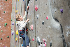 Kid rock climbing. Little active boy rock climbing at indoor gym Royalty Free Stock Images