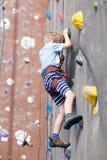 Kid rock climbing Stock Photos
