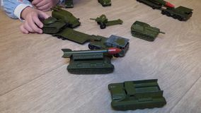 Kid rolls old military vehicles - metal cars colored in khaki