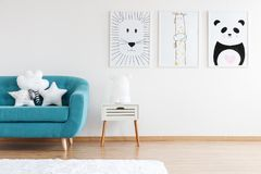 Kid room with turquoise couch. Simple kid room with turquoise couch, white carpet and posters with animal drawings stock images