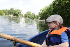 Kid rowing boat Stock Photos