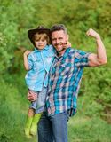 Kid in rubber boots. happy dad in forest. human and nature. family day. happy earth day. Eco farm. small boy help. Muscular father in farming. father and son in stock image