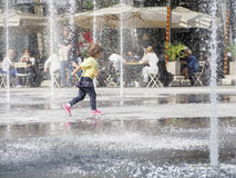 Kid running through a fountain royalty free stock image