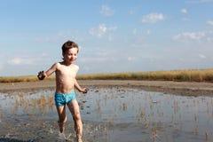 Kid running in healing mud. Kid is running in healing mud, Russia Royalty Free Stock Photography