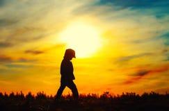 Kid walking on meadow. Silhouette of sad single child on sunset sky Stock Photo