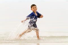 Kid running on the shore Stock Photos