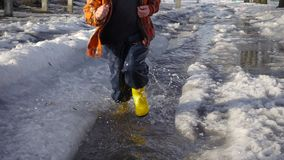 Kid running at the spring creek with melting ice stock footage