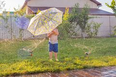 A kid running through water drops of the fontain on front yard with automatic watering system. Exciting games outdoor stock images