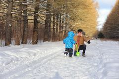 Kid running in winter park and have fun with family stock photos