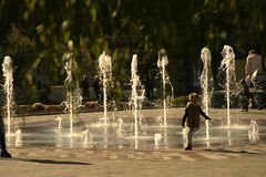 The kid runs away from the stream of water in the fountain. stock image